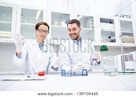 science, chemistry, biology, pharmacy and people concept - young scientists with pipette and flask m