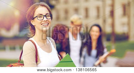 education, campus, friendship and people concept - group of happy teenage students with school folde