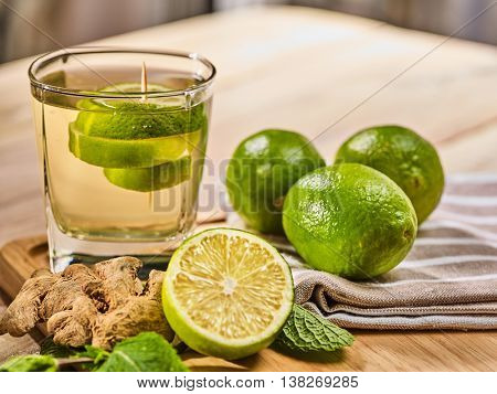 Healthy detox drink with ginger cocktail . On wooden boards glass with green tea and mint. A mint gi