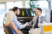 auto business, car sale, and people concept - happy couple with dealer shaking hands in auto show or poster