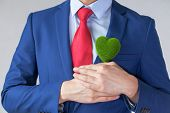 Businessman In Suit Holding A Green Heart Shape poster