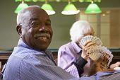 image of senior adult  - Senior man playing bridge - JPG