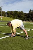 image of hamstring  - handsome middle age senior man stretching legs hamstrings exercising on sports field touching toes - JPG