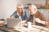 Excited Mature Pensioners Watching Video On Laptop In Kitchen. They Are Drinking Tea With Cookies An poster