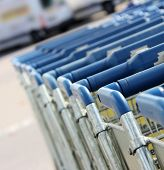 stock photo of parking lot  - many shopping carts in a row are waiting for using - JPG