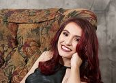 Attractive Smiling Brown-eyed Red-haired Teen Girl In A Black Prom Dress Sitting In A Chair poster