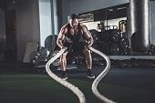 Muscular Powerful Aggressive Man Working Out With Rope In Functional Training Fitness Gym poster