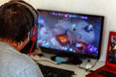 Back View Of Concentrated Young Gamer In Headphones Using Computer For Playing Game At Home. Compute poster