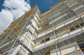 scaffolding near a new house, building exterior, construction and repair industry, white wall and wi poster