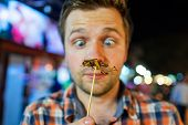 Caucasian Young Male Eating Cricket At Night Market In Thailand. Eating Insect Concept poster