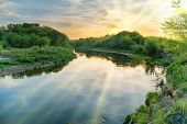 Sunset Over River. Landscape With Green Trees, Dramatic Sky, Clouds, Sun And Sunrays poster