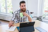Portrait of a confident self-employed young man smiling and looking at camera, while sitting at desk poster