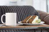 White Blank Coffee Mug Mock Up. The Mug Is Next To A Piece Of Carrot Cake With A Sofa In The Backgro poster