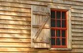 Red Window And Shutter In A Weathered Wood Building poster
