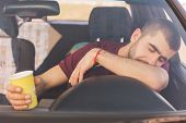 Fatigue Overworked Tired Male Driver Has Long Trip In Car, Makes Stop To Have Rest, Has Nap On Helm, poster