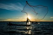 Un-identified Silhouette Fisher Man On Boat Fishing By Throwing Fishing Net To River During Sunset I poster