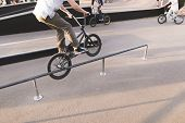 The Young Man Performs The Bmx Trick On The Railing In The Skip Box. Legs And Bmx Perform A Trick. W poster
