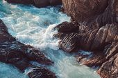 Sea Waves Crashing Against The Rocks In The Evening Sunlight poster