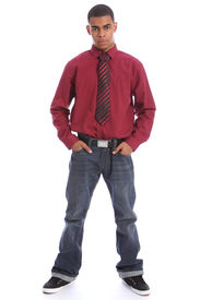 stock photo of teenage boys  - Smartly dressed good looking young African American teenage student boy standing with serious expression on his handsome face wearing casual jeans and formal long sleeved shirt and necktie - JPG