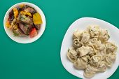 Dumplings On A White Plate On A Green Background. Top View Of Dumplings With Vegetable Salad. Asian  poster