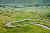 Hairpin Turn Of Rural Road In Vibrant Green Alpine Meadows,asphalt Road With Hairpin Bend In Flower  poster