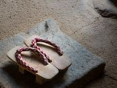 Traditional Japanese Wooden Geta Shoes Standing On Stone Entrance Steps To Temple. Still Life Of Old poster