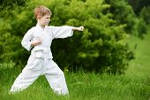 One little boy in white kimono during training karate kata exercises in summer outdoors