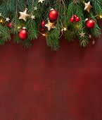 Christmas border with fir branches, red baubles and gold stars on the wooden board painted in dark-r poster