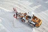 Snow plow machine clearing snow from roads after heavy snowfall in the Alps poster