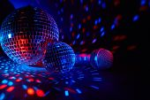 Glittering mirror disco balls and microphone on dark background with red blue lighting. Copy space.  poster
