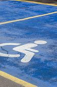 Disabled Parking Spaces In An Empty Parking Lot. Blue And White Symbol Is Drawn On The Pavement. Tra poster