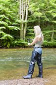 stock photo of fisherwomen  - woman fishing at river - JPG