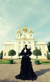 Beautiful woman in black dress posing next to the palace. Dark Queen.