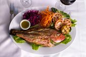 Full Cooked Tilapia Served With Vegetables And Fish Sauce Complimented With Vine
