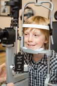 stock photo of slit  - Smiling boy undergoing eye examination test with slit lamp in store - JPG