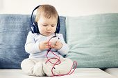 foto of pretty-boy  - Cute baby boy sitting on sofa and listening music at headphones while  looking at iphone - JPG