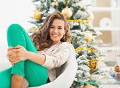Portrait Of Happy Young Woman Relaxing Near Christmas Tree