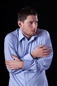 stock photo of shivering  - An adult sick man in a shirt standing and shivering - JPG