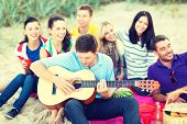 Постер, плакат: summer holidays vacation music happy people concept group of friends with guitar having fun on
