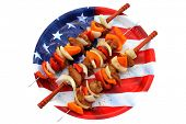 image of kebab  - Genuine American Chicken, Onion, and Bell Pepper Shish Kebab on Metal Skewers with Wooden handles on an American Flag Plate.  Kebab is a Middle Eastern dish of pieces of meat, on a skewer.