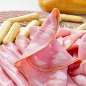 image of charcuterie  - closeup of some slices of mortadella and some bread sticks - JPG