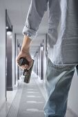 stock photo of bodyguard  - Man holding gun against an corridor background - JPG