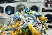 stock photo of dirty-laundry  - Pile of dirty laundry in laundrette, close-up
