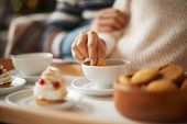 picture of biscuits  - Hand of female with biscuit during tea time in cafe - JPG