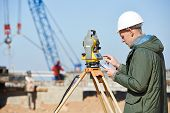 stock photo of geodesic  - Surveyor builder worker with theodolite transit equipment at construction site outdoors during surveying work - JPG