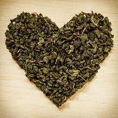 Постер, плакат: Green Tea Leaves Heart Shaped On Wooden Surface