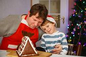 foto of gingerbread house  - Dad and his little adorable child having fun with baking a gingerbread cookie house at christmas time home - JPG