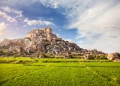 stock photo of hanuman  - Rice plantation near Hanuman monkey temple on the big stone hill at blue sky in Hampi Karnataka India - JPG