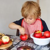 stock photo of pie-in-face  - Adorable little boy helping and baking apple pie in home - JPG