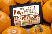 stock photo of happy thanksgiving  - Happy Thanksgiving word cloud on a digital tablet surrounded by pumpkins - JPG